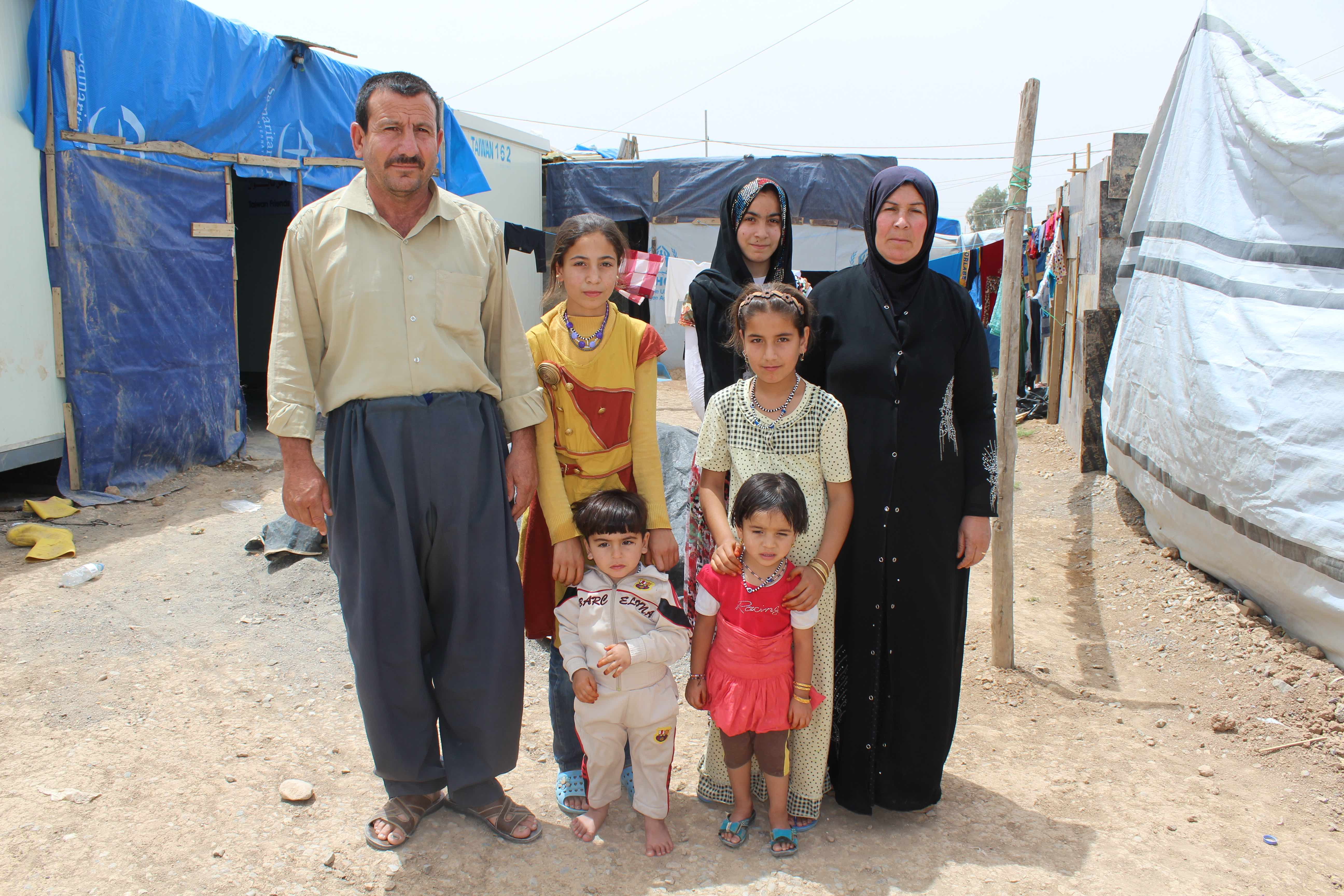 Walid, a 46-year-old handyman from Bartella, a small town on the outskirts of Mosul. He lives in Harshm IDP camp in Erbil, Kurdistan. Pictured here with his two sons and four daughters. Other family members live nearby in the camp. The family is Shia Shab