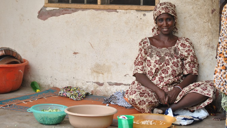 Aisha sits in front of her house in Yola, preparing dinner for her children and the host family. She has fled Borno almost a year ago when her village was attacked by Boko Haram militants.