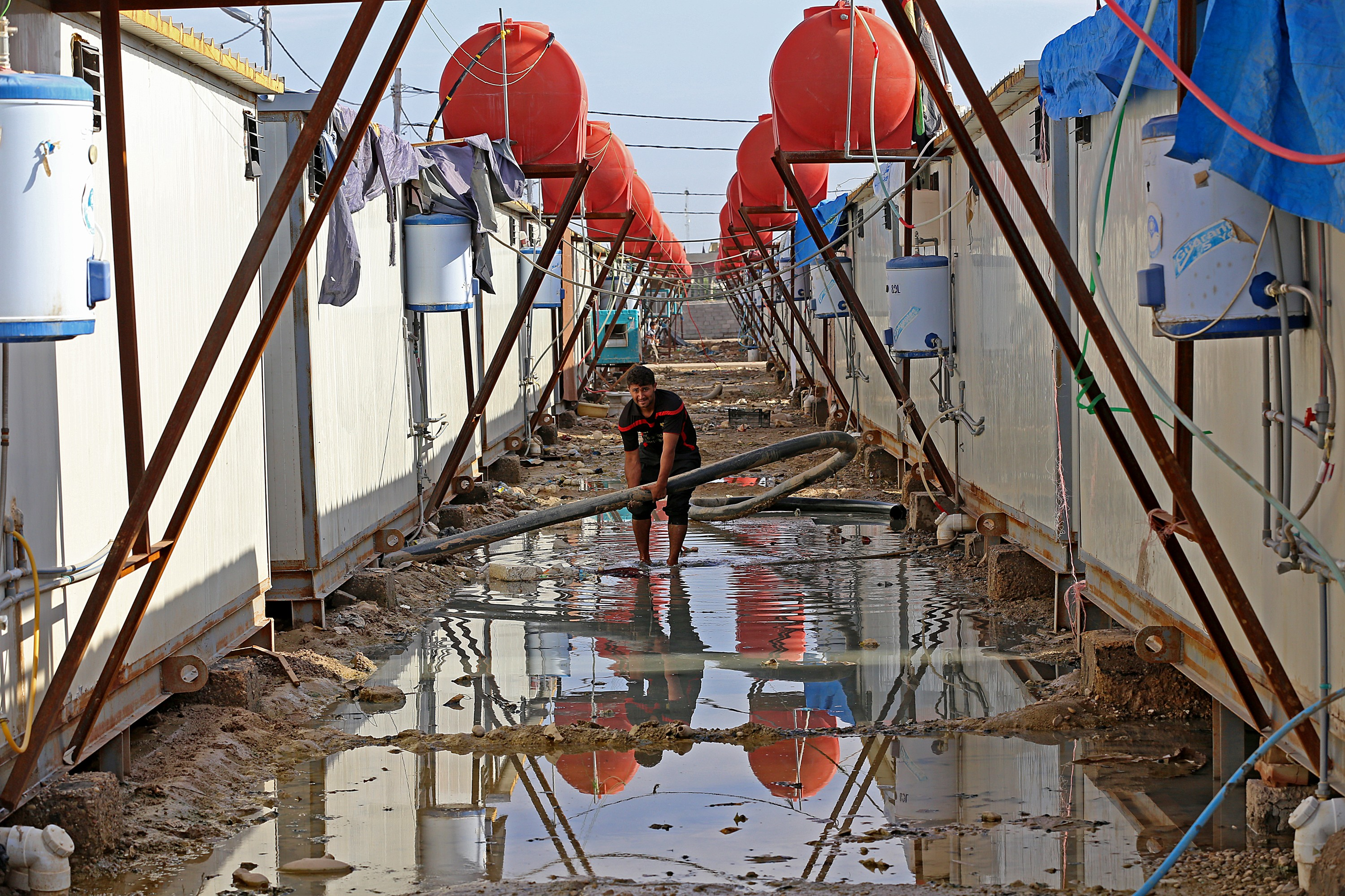 On 04 November a man fixes water pipes while standing in floodwater behind a set of shelters in Nabi Younis IDP camp in Nahrawan, a suburb of Baghdad. Heavy rain in Iraq in late October inundated several areas of the country considered vulnerable to the s