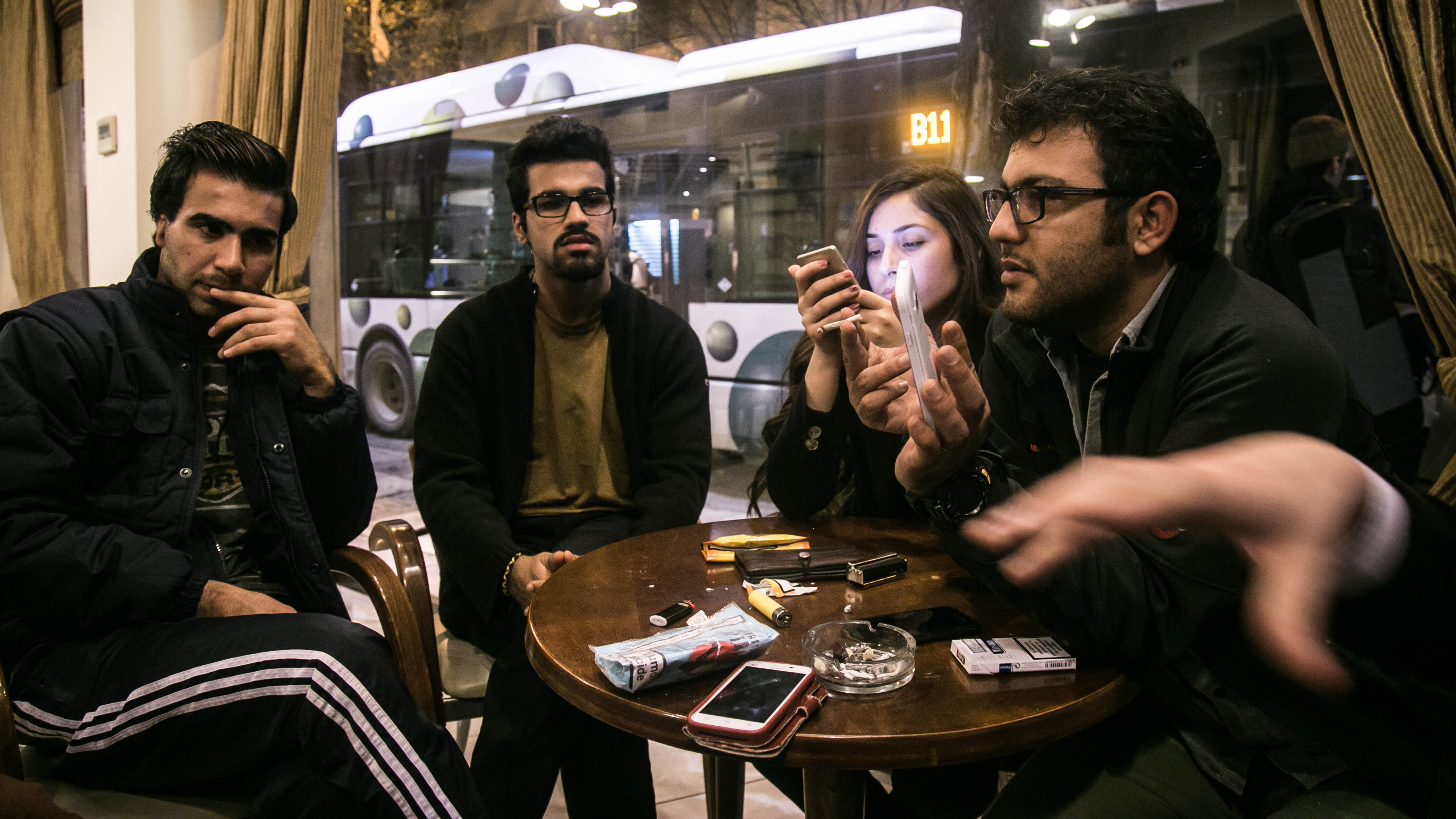 Aral Kakl, a Kurdish Iraqi journalist, his Syrian wife Shevin, his brother Rewan and some other refugees who have applied for the relocation programme, kill time in the cafeteria of their Athens hotel