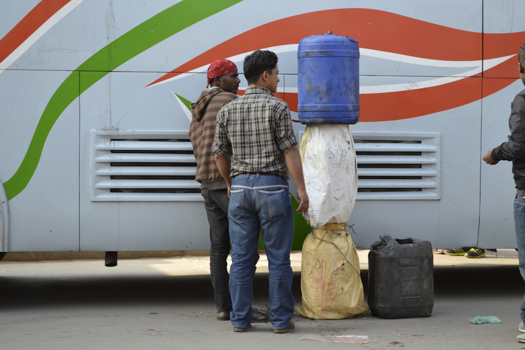 Men in Nepal's capital, Kathmandu, unload fuel smuggled over the border from India on a bus in January 2016