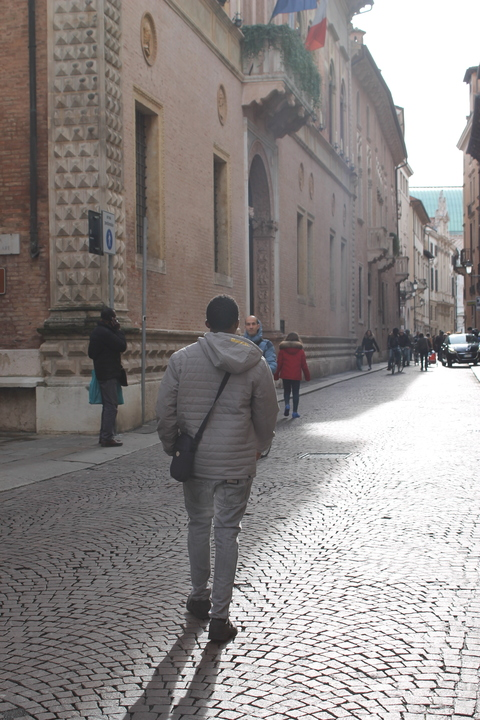 Lamin walks through the cobbled streets of his new home town
