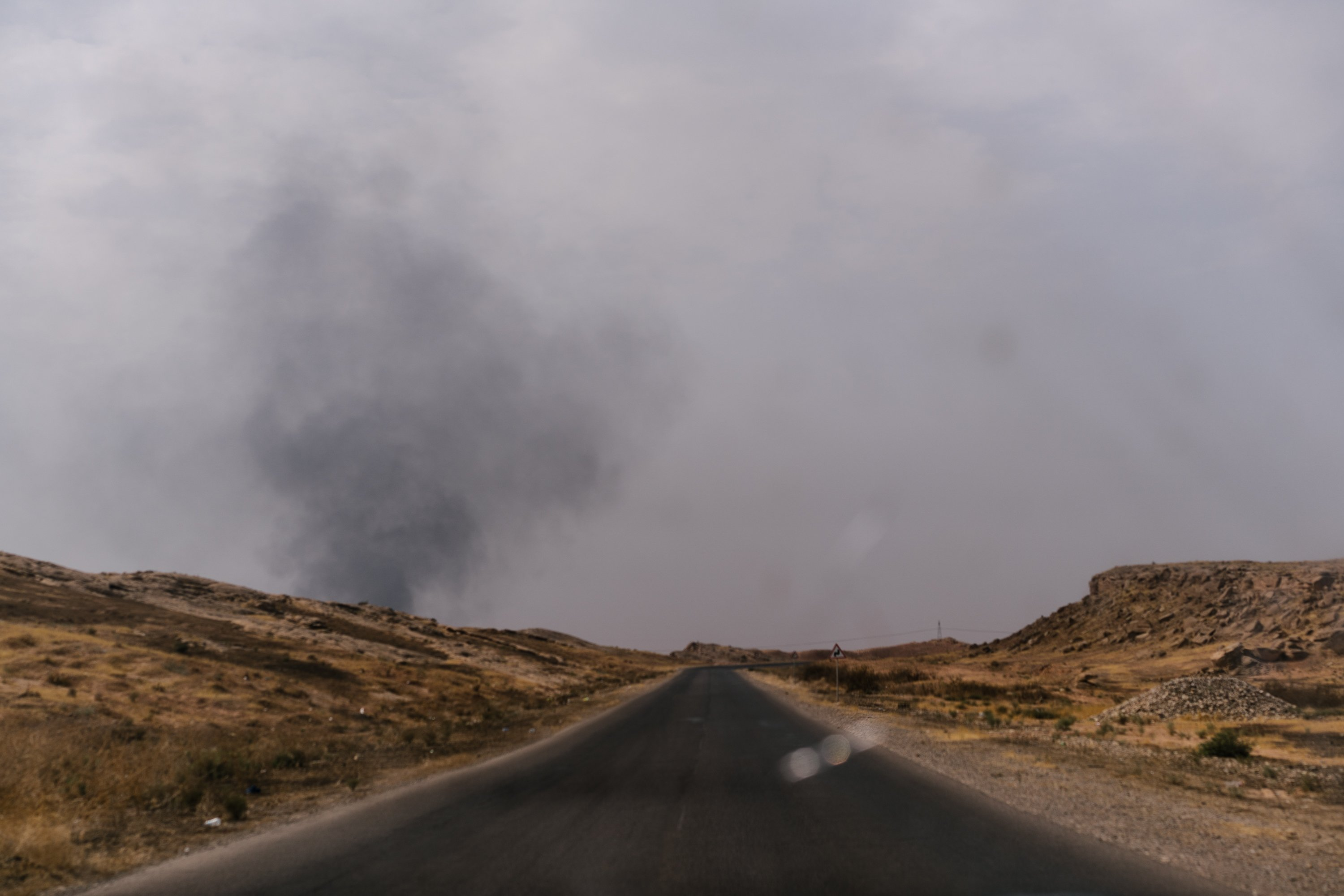 A cloud of smoke over an empty road