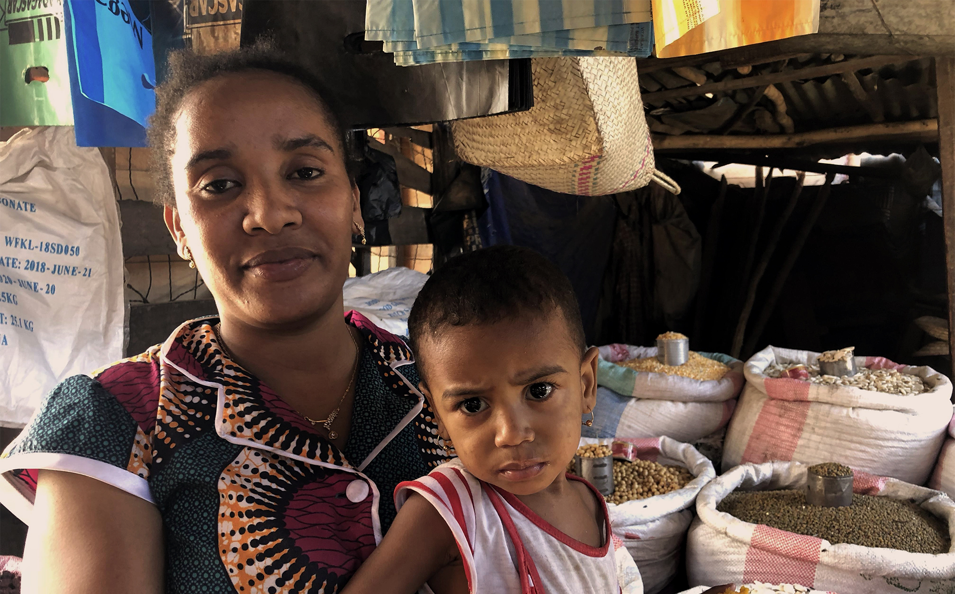 Woman and child in front of a food market stall