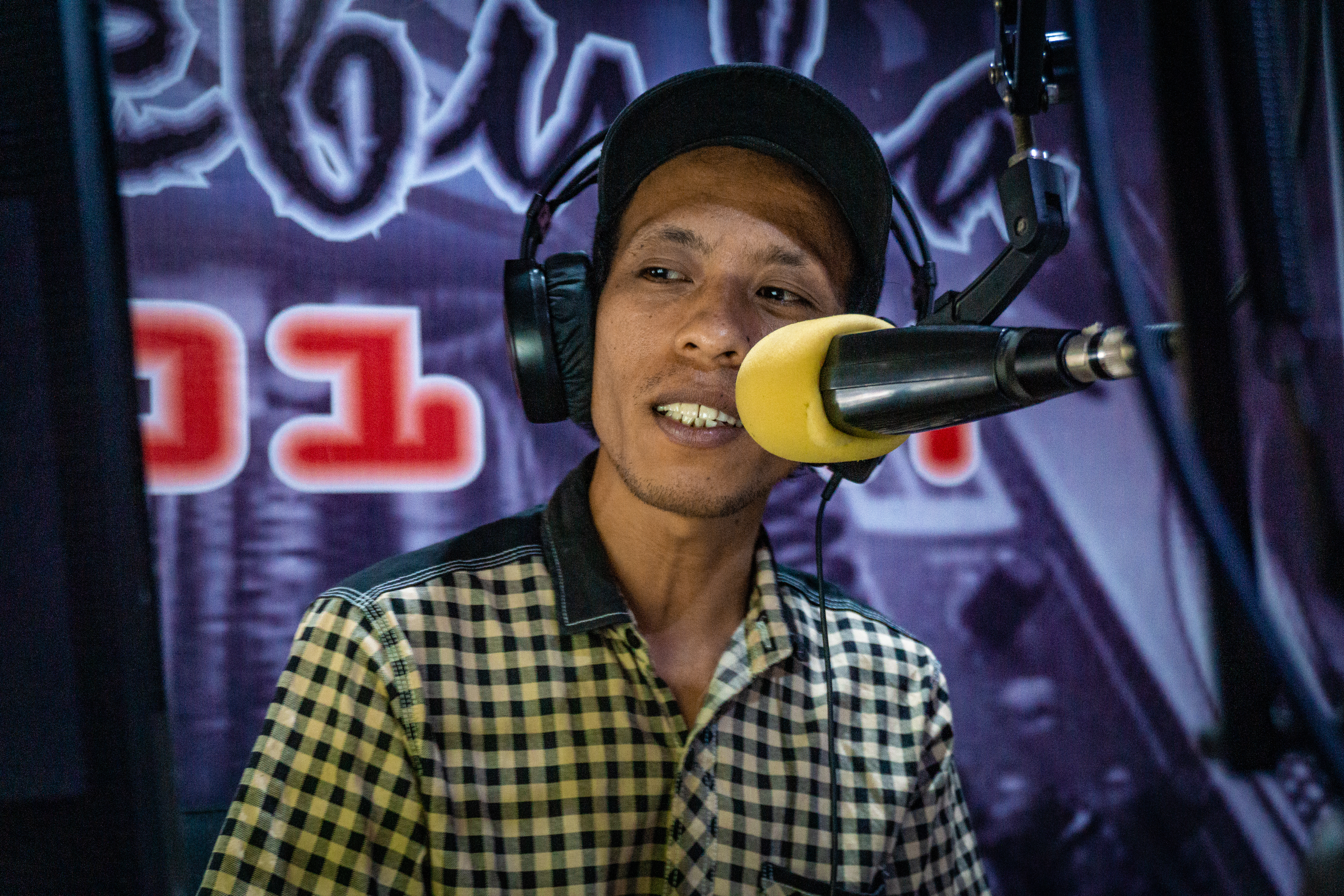 Delano Indonesian journalist on mic for Radio Nebula in Sulawesi