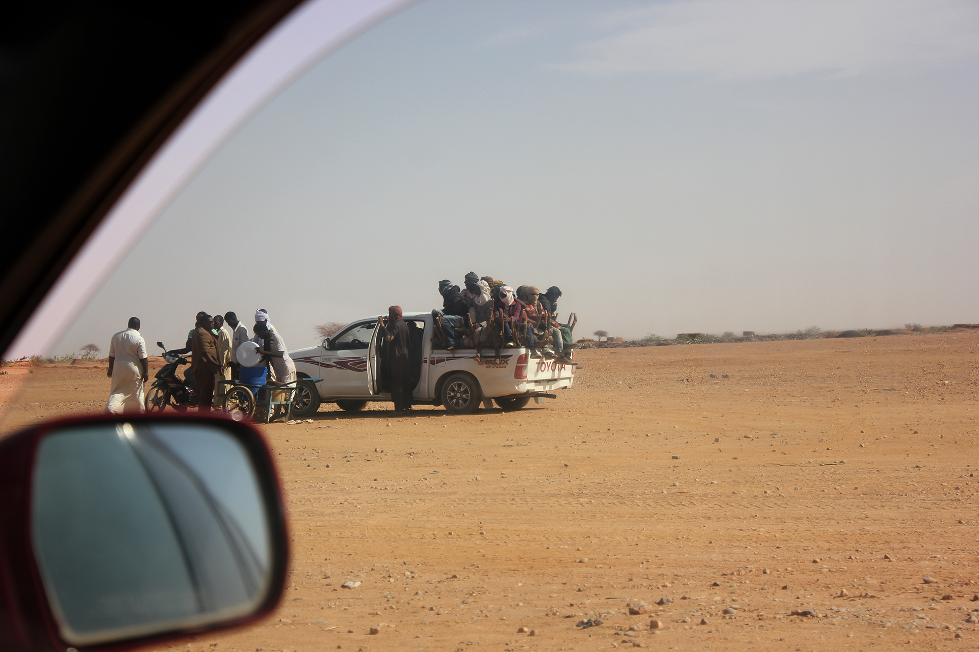 Migrants load into the back of a pickup at a checkpoint outside of Agadez, Niger before beginning the long journey across the Sahara to Libya, March 2018.