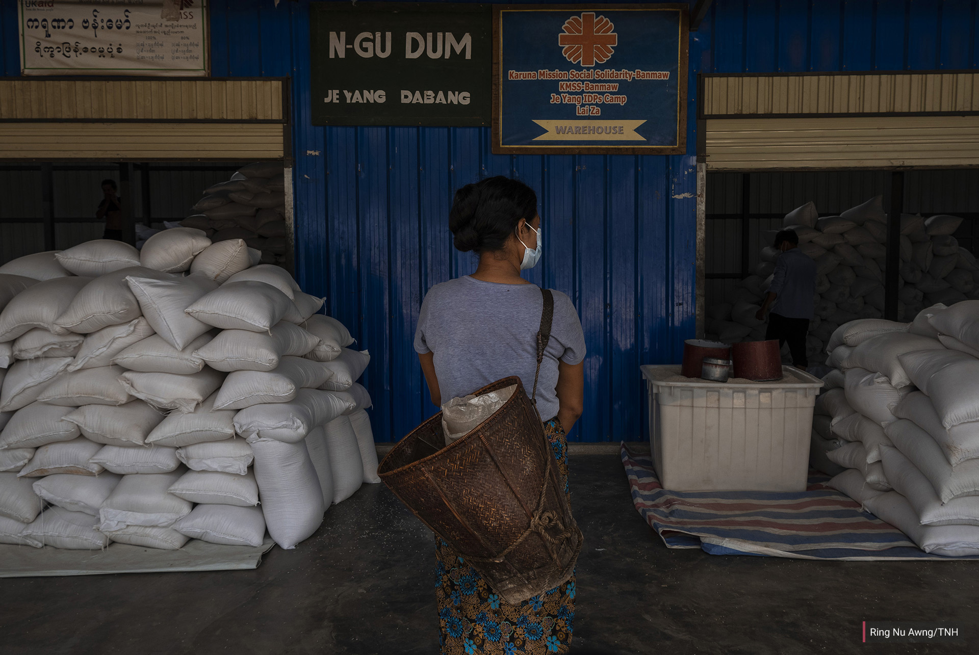 A woman in Je Yang IDP camp collects her family's rations