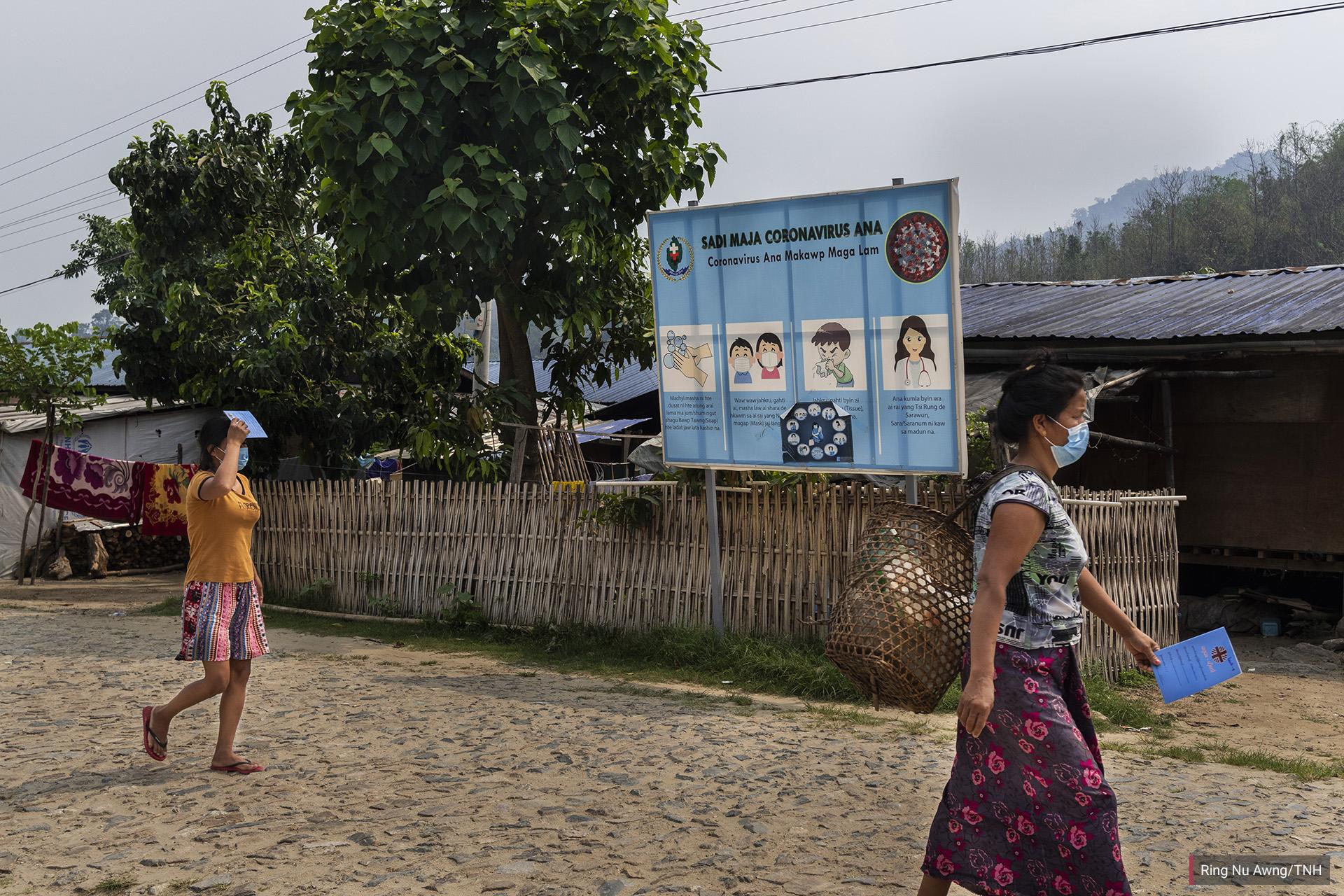 Women walk past a vinyl banner in Jinghpaw