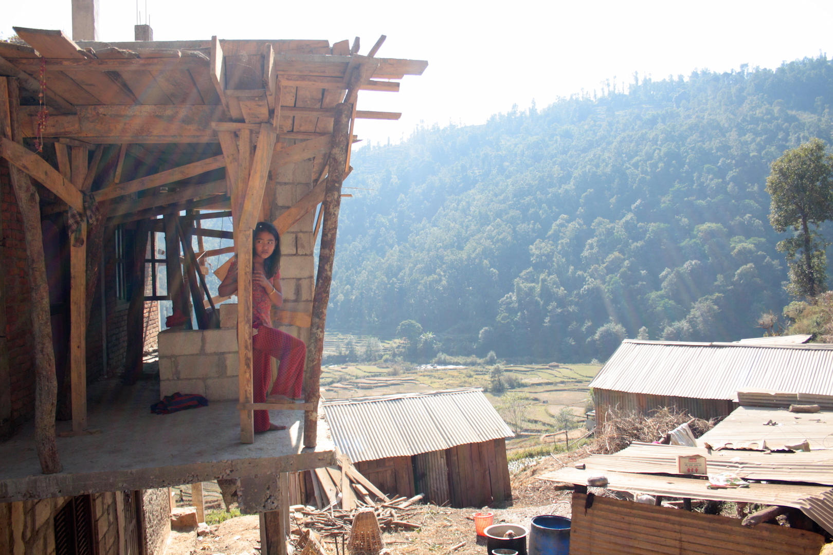 A young girl rests on a beam in her house in Sindhupalchok, Nepal, which is being rebuilt after the 2015 earthquake