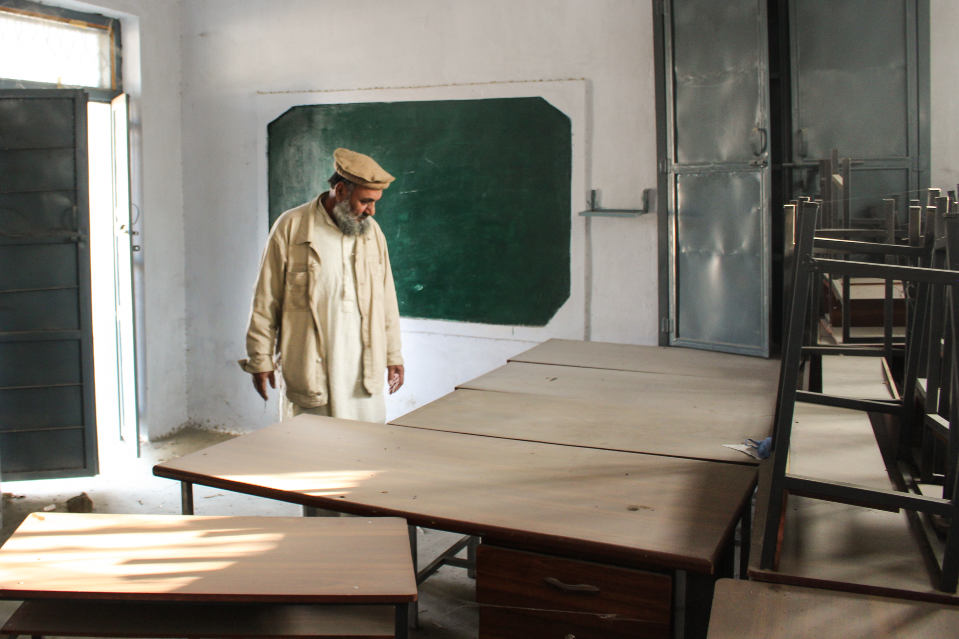 Hanif Ullah, a local education activist, inspects dust-covered desks and chairs at a shuttered school in Maminzo village, Pakistan.