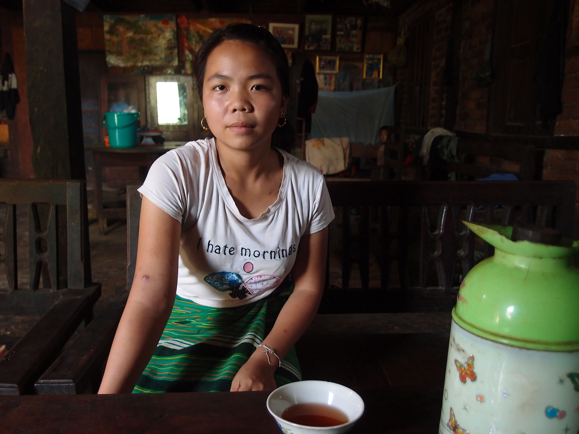 Portrait of young person in Myanmar with tea and a shirt that says