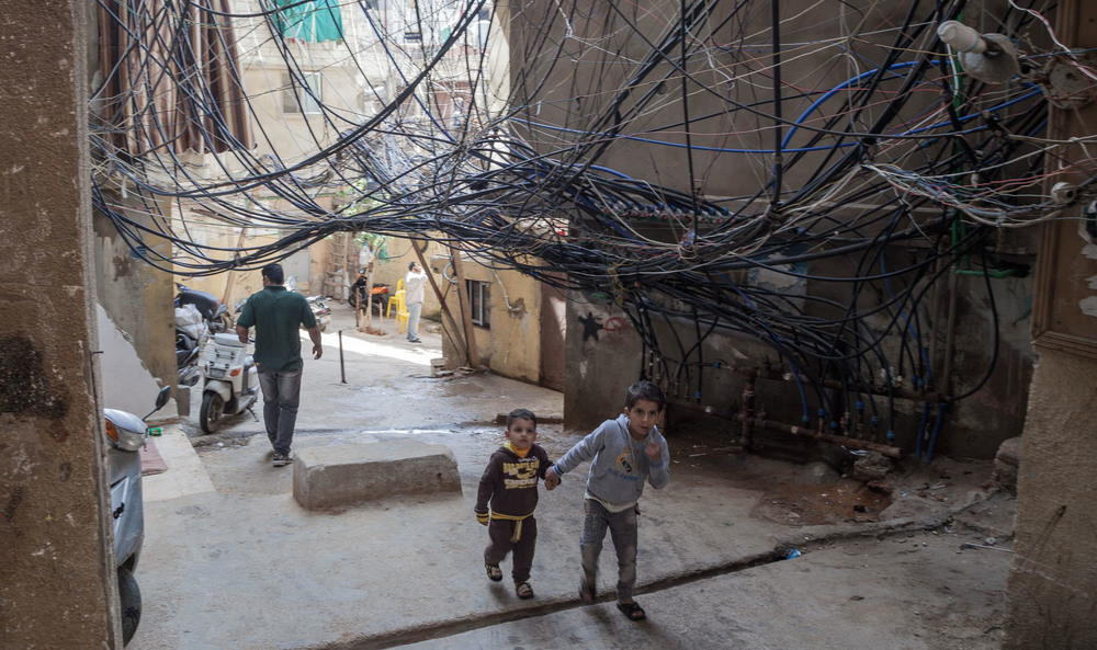 Two children walk under a nest of loose wires in the Bourj el-Barajneh neighborhood of Beirut.