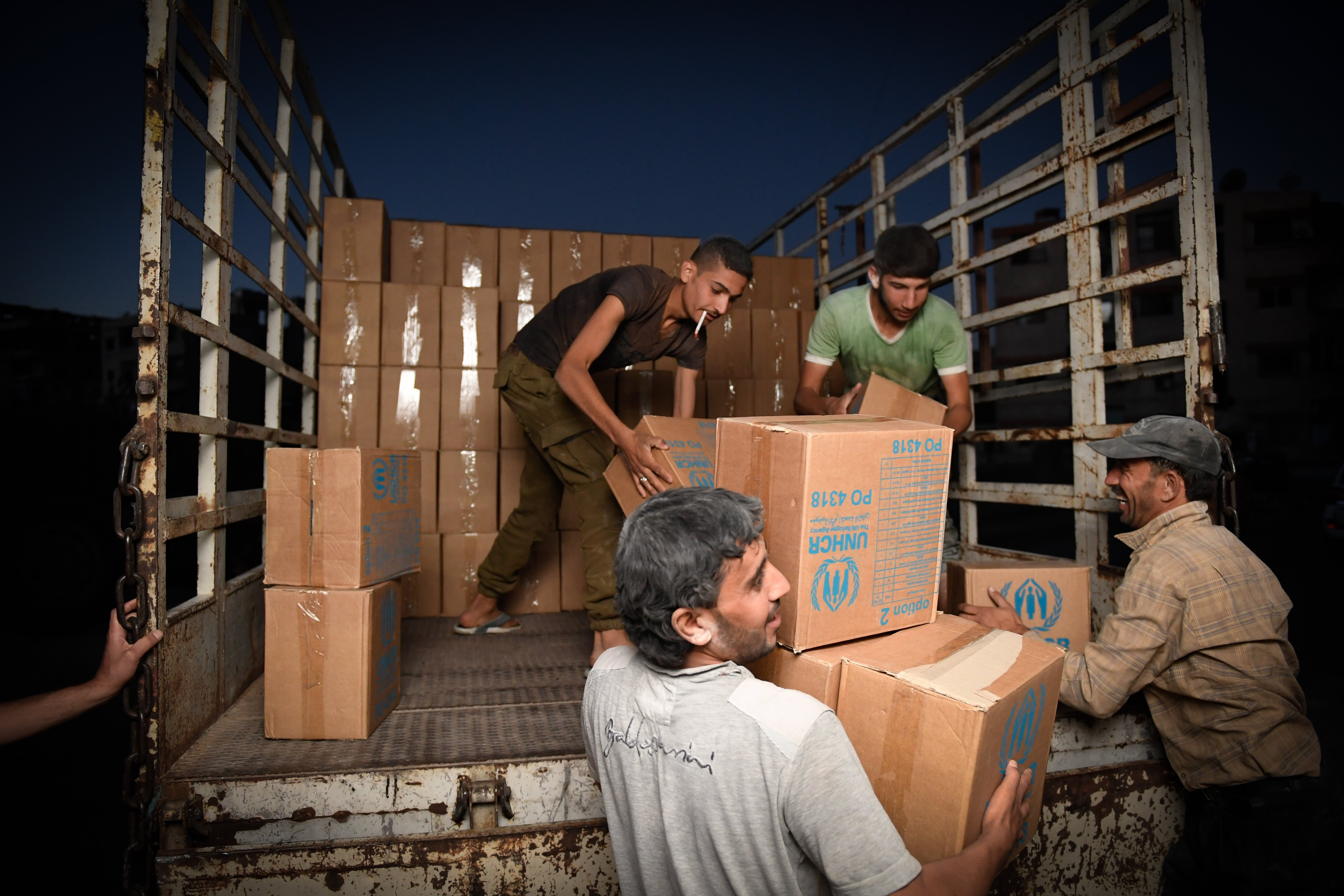 Volunteers and aid workers offload boxes of food and medicine from UN inter-agency trucks delivering desperately needed supplies to Mouadamiyeh in rural Damascus