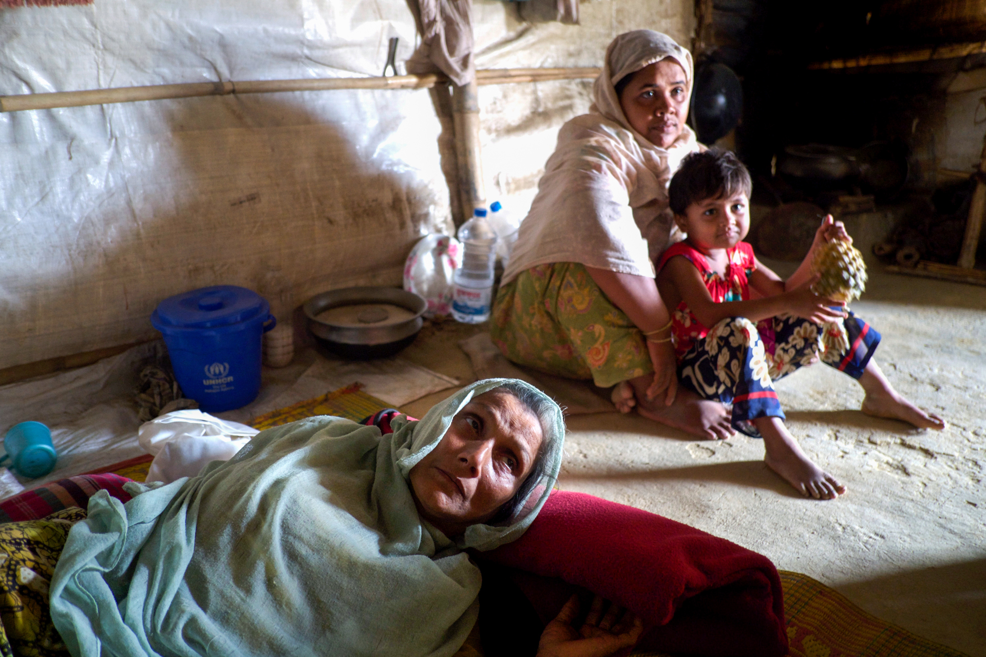 A woman in the foreground lays on her side while a younger woman and a child sit behind her on a dirt floor