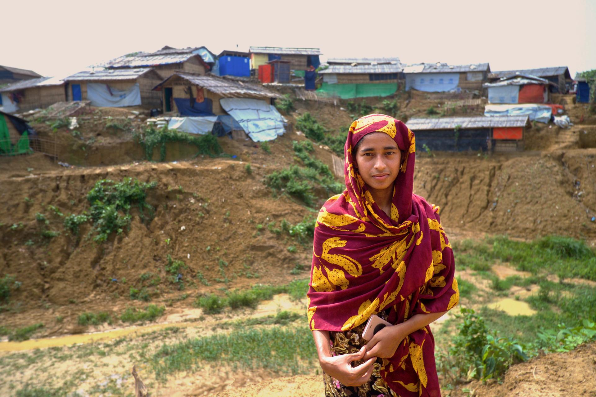 A woman looks at the camera in front of a refugee camp in Bangladesh