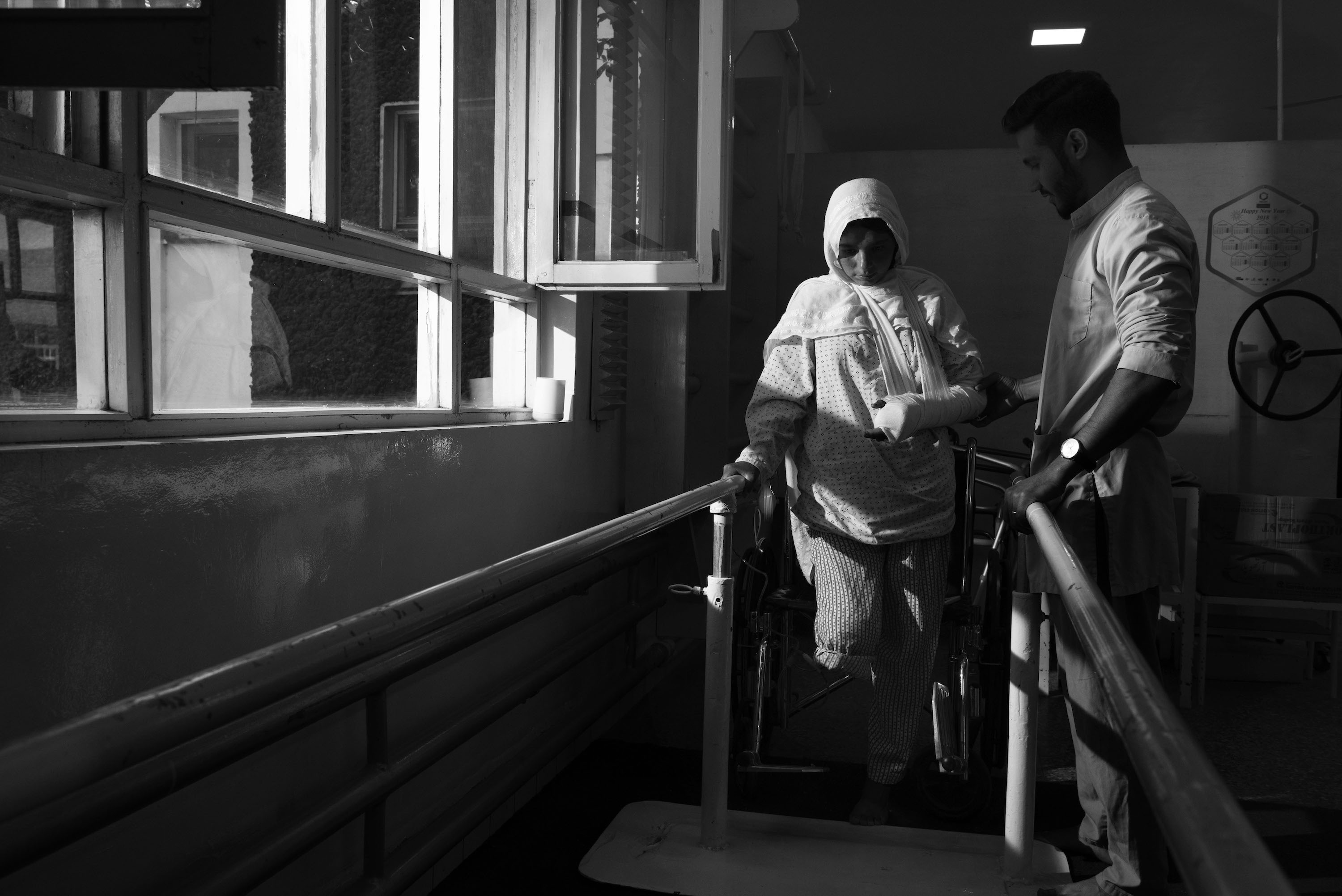 A woman walks with help of railings and medical staff