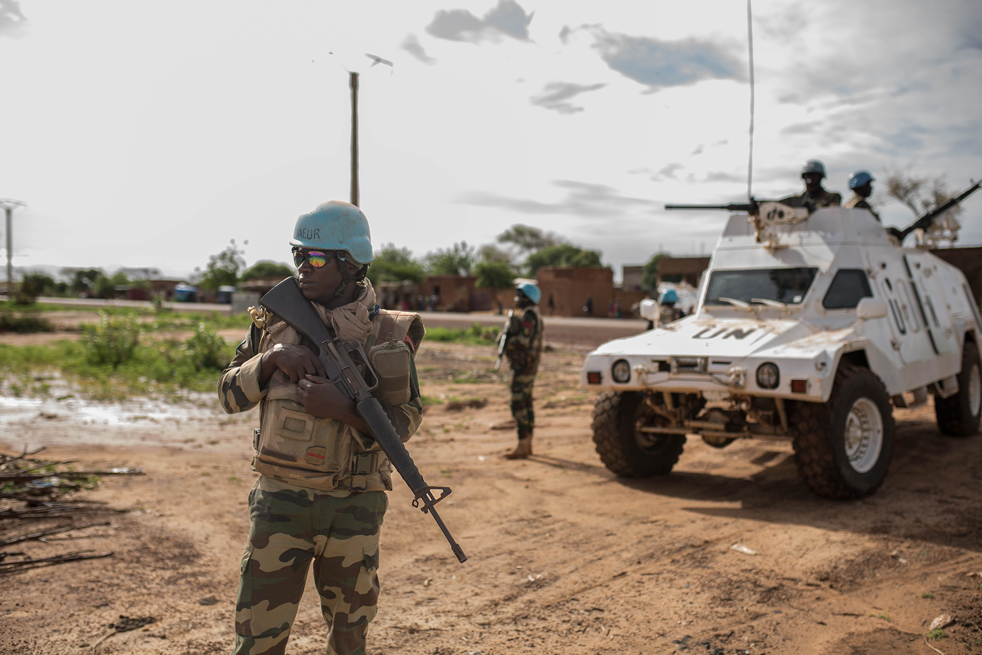 A UN peacekeeper with a gun looking out in front of a UN tank