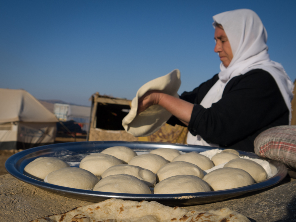 A Yazidi woman prepares bread dough on top of Mount Sinjar