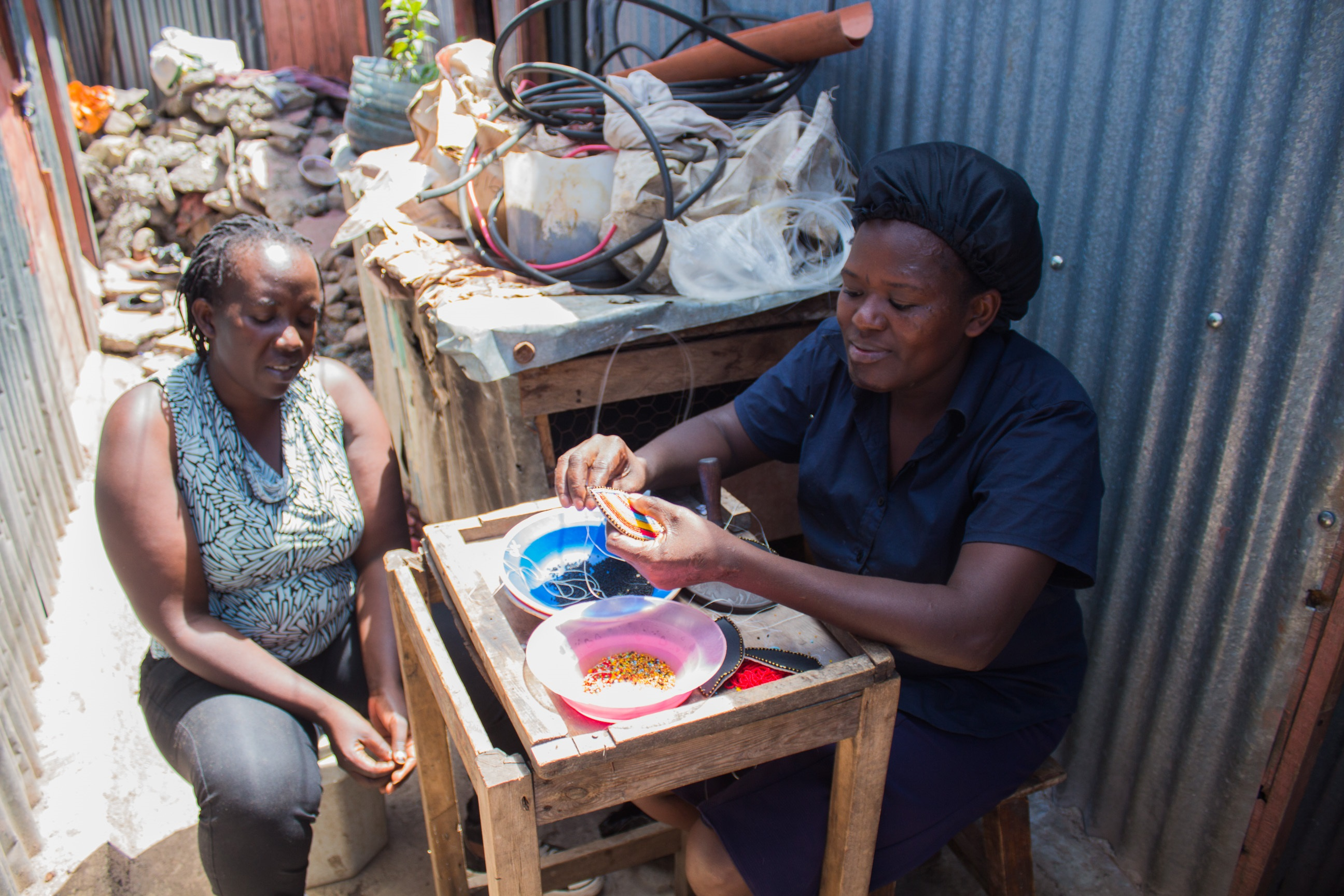 Resident Christine Wayua strings beads in Mukuru