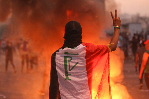 An Iraqi protester gestures the v-sign during a demonstration in Baghdad on 2 October 2019.