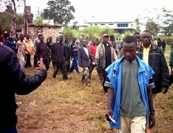 [DRC] Militiamen queue at a disarmament site in Bunia, Ituri District.