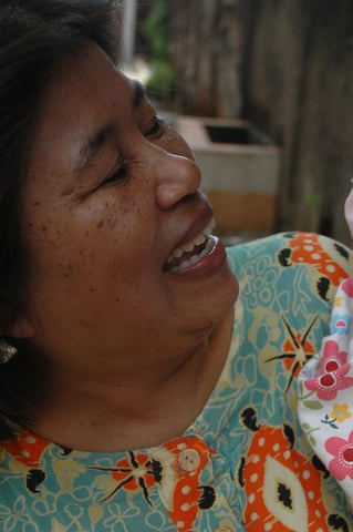 Dede Jafar playing with her ten month old granddaughter. Dede did not hesitate for a moment to have her only granddaughter circumcised. Female circumcision is still widely practised in Indonesia, after the government ban in 2006