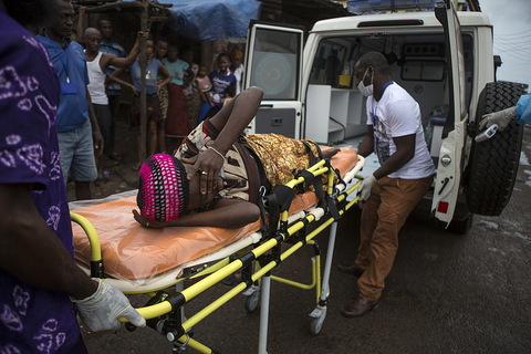 Kadie Sise, who is pregnant and suspected of having Ebola, lies on a stretcher as health workers lift her into an ambulance, in Freetown,