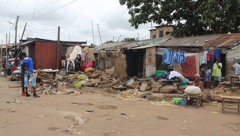 A family sits outside destroyed homes in Accra's Nima neighbourhood, following heavy rains and flooding on 3 June.