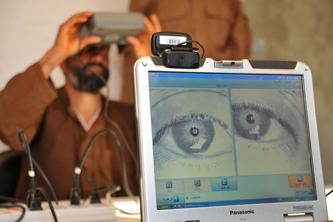 A member of the Afghan Local Police (ALP) looks into a biometric eye scanner during in-processing into the ALP by members of the Afghan Ministry of Interior in Gizab district, Uruzgan province, Afghanistan