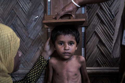 Health workers measure Rohingya child
