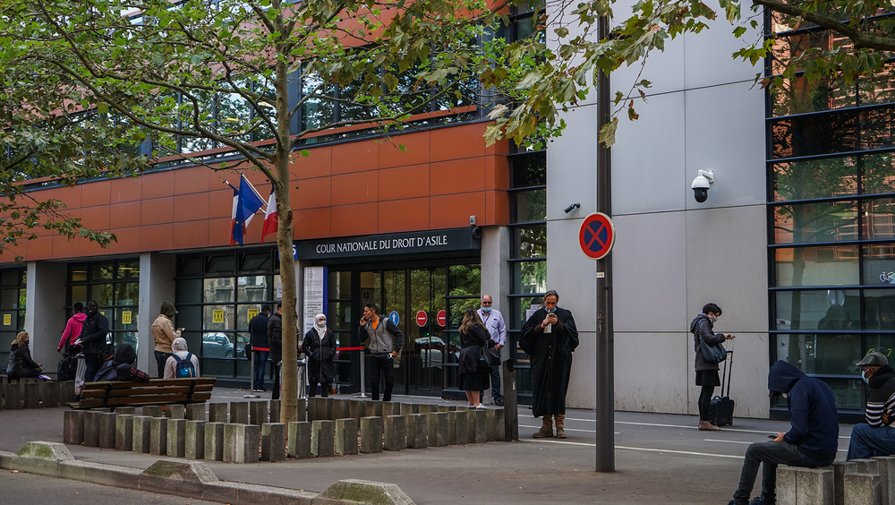 People line up outside the Cour Nationale du Droit d'Asile in Montreuil (CNDA), just east of Paris, on October 12. Due to the ongoing pandemic, defendants are not allowed inside the court until the hour of their assigned hearing.