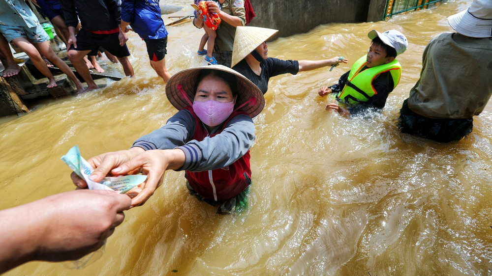 A resident gets money from a volunteer at a flooded area in Quang Binh province, Vietnam, on 23 October 2020.