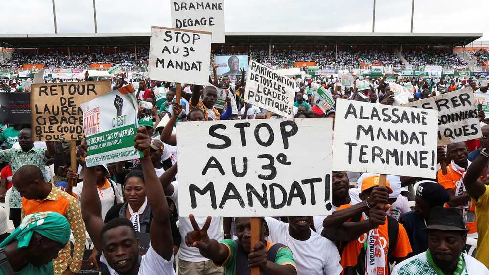 "Supporters of Côte d'Ivoire's opposition coalition parties hold signs during a stadium rally to protest against president Alassane Ouattara's bid for a third term in Abidjan, Côte d'Ivoire, 10 October, 2020. The front sign reads: ""Stop to a third term""."