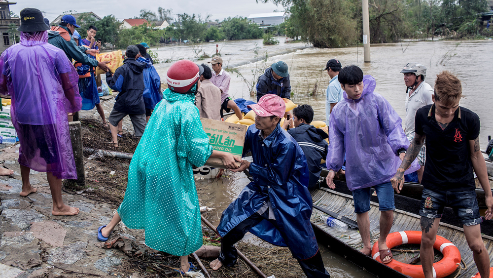 Volunteers deliver aid packages to residents affected by heavy floods in Quang An commune, in Thua Thien Hue, Vietnam, on 20 October 2020.