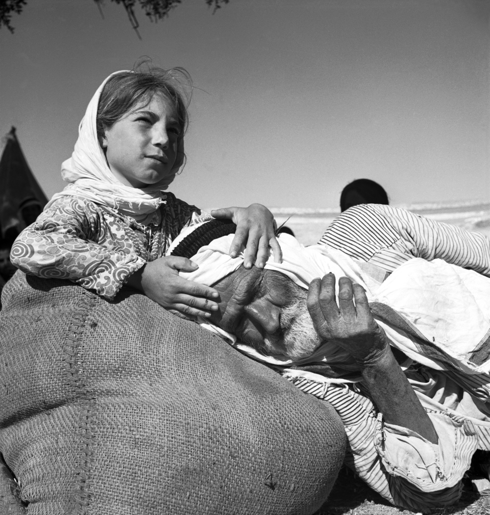 Black and white photo of an old bearded man with his head on a burlap sack with a young girl holding it and looking into the distance