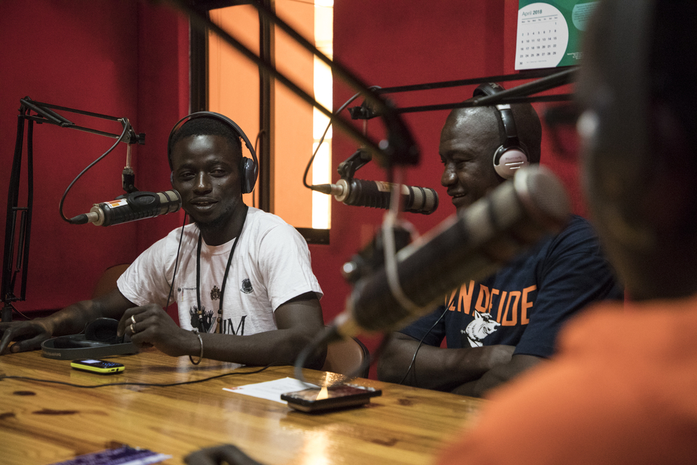 A group of young men in a radio studio at mics
