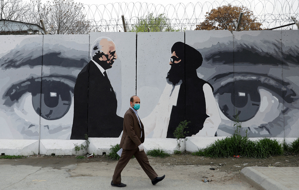 An Afghan man wearing a protective face mask walks past a wall in Kabul