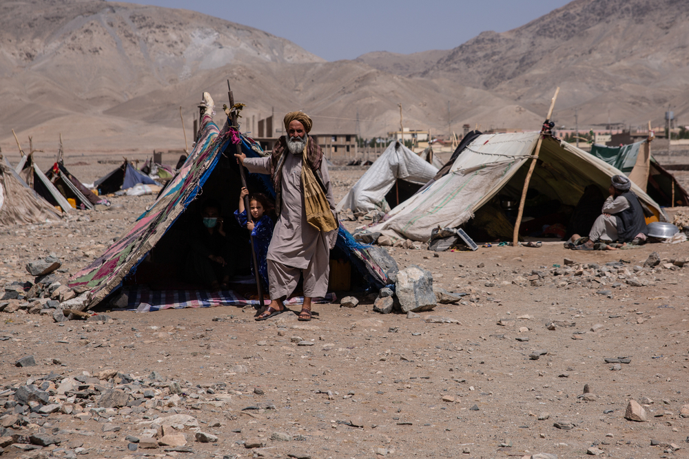 A man stands next to a tent in a makeshift camp.