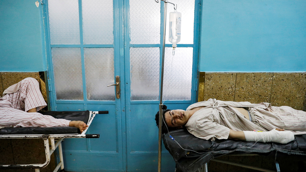 Injured men receive treatment in hospital after sustaining wounds from a blast at a wedding hall in Kabul, Afghanistan 18 August, 2019