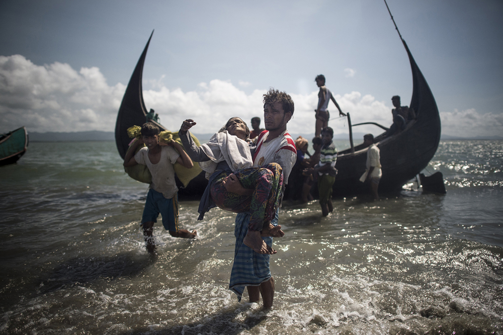 A Bangladeshi man helps Rohingya Muslim refugees to disembark from a boat on the Bangladeshi shoreline of the Naf river after crossing the border from Myanmar in Teknaf on 30 September 2017.
