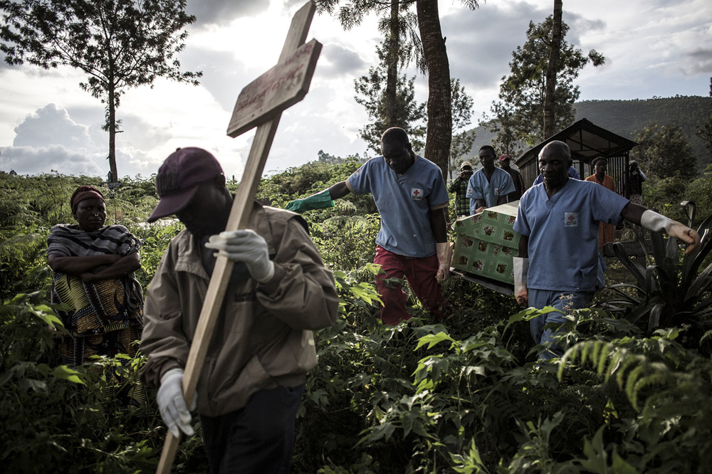 Health workers carry a coffin containing a victim of Ebola virus on 16 May 2019 in Butembo, DRC.
