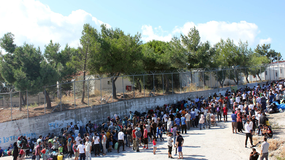 Asylum seekers wait outside the Moria processing centre on the Greek island of Lesvos.