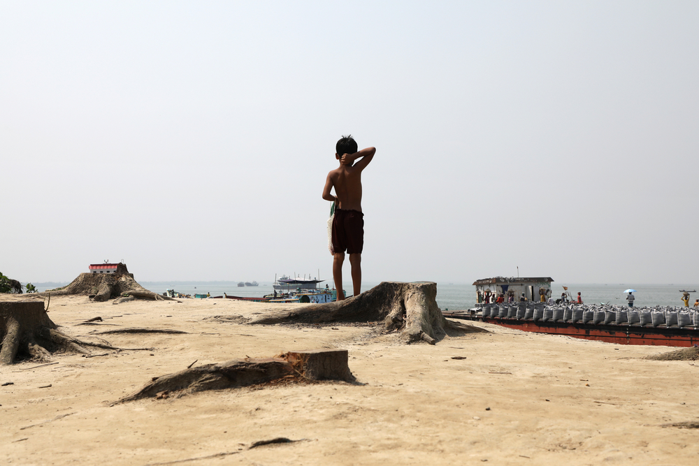 Photo of a child looking out at the Padma river in Bangladesh as river protection work happens