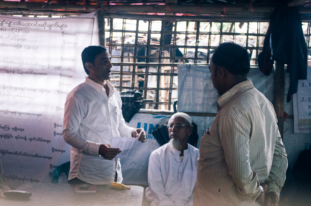 Three adult men in a white have a discussion inside a temporary structure
