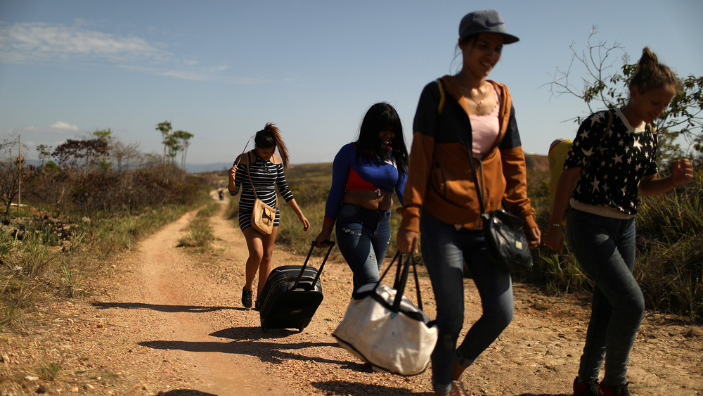 Venezuelan migrants walk along a trail