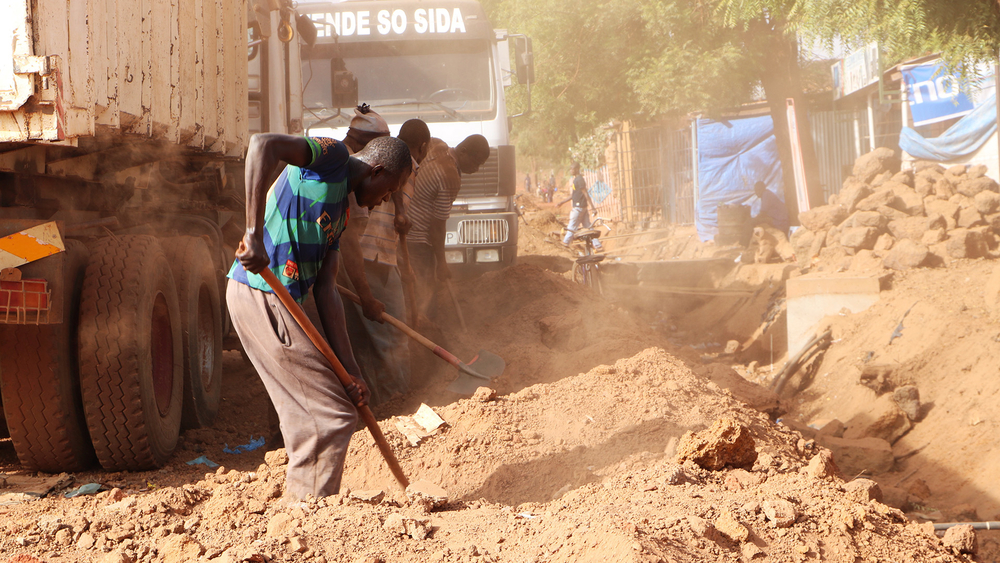 A group of men dig ditches along the main road in Tougan