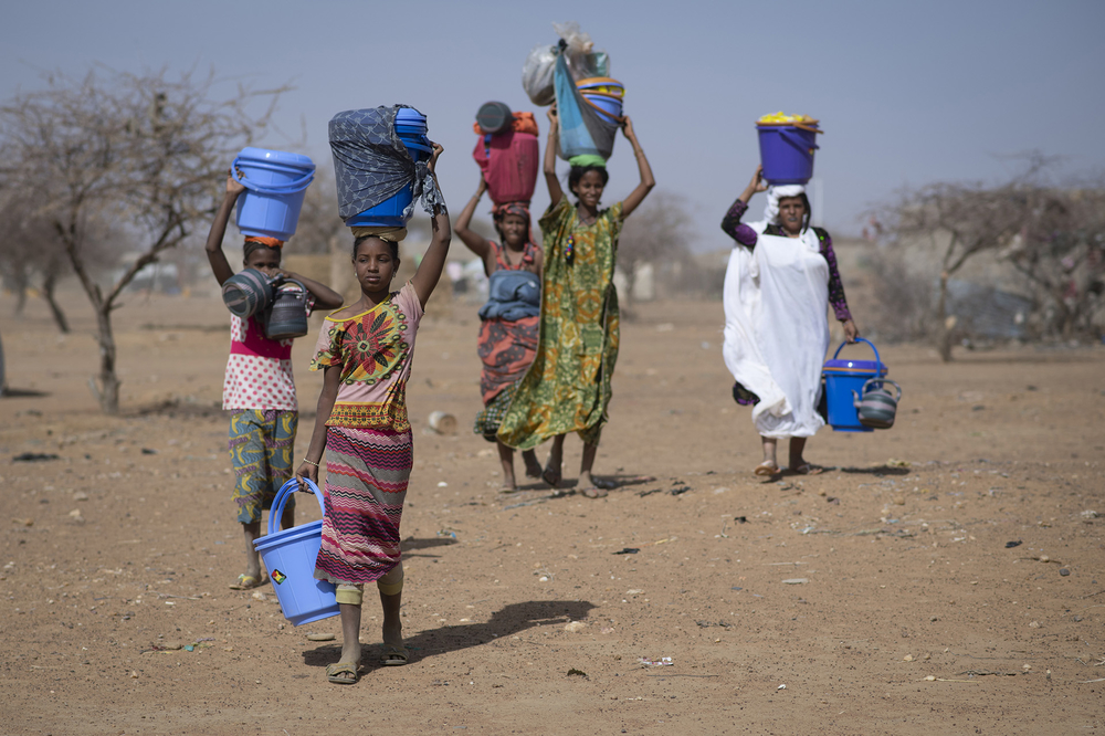 Malian refugees carry new dignity kits in Goudoubo camp in Burkina Faso