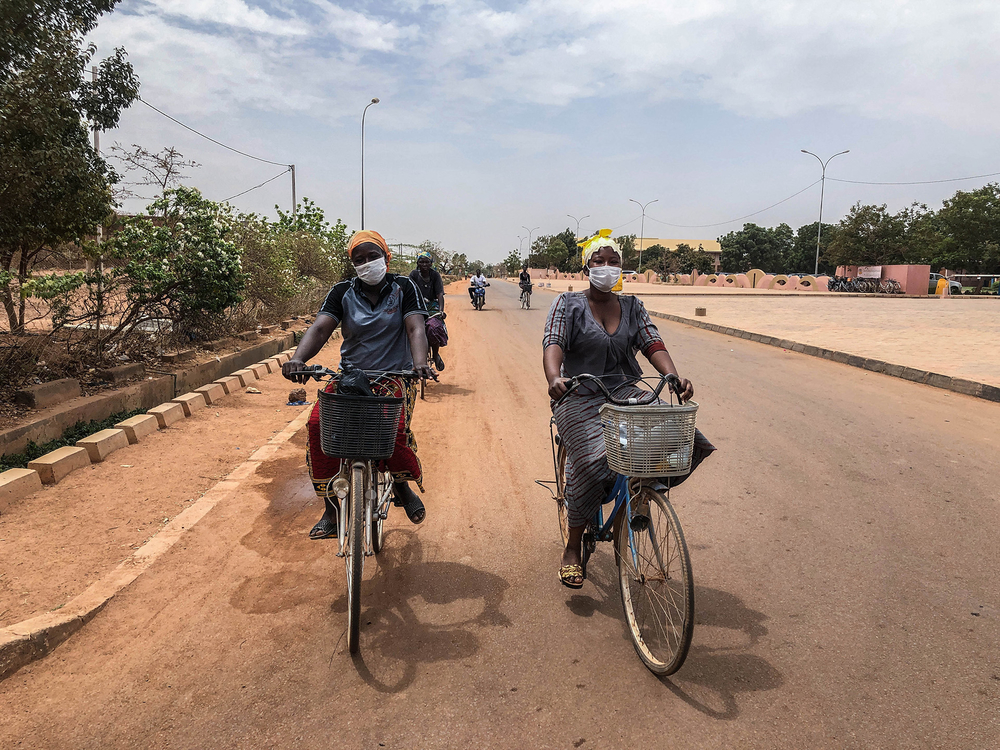 Ouagadougou residents wear masks while cycling