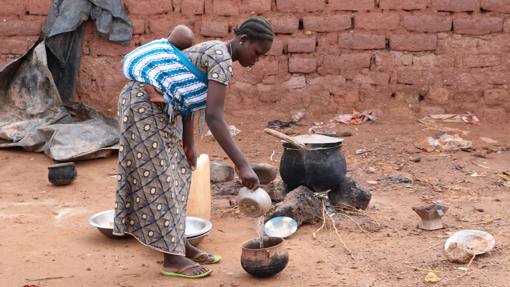 A woman cooks for a family of displaced people in Kongoussi