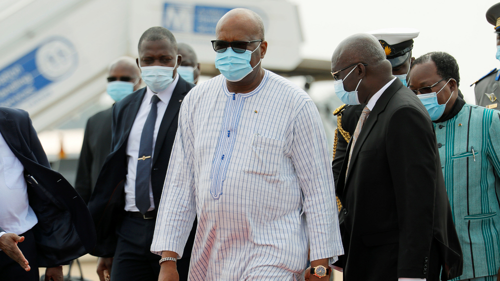 A photo shows Burkina Faso's President, Roch Kabore, walking with a face mask. Burkina Faso's leader, Roch Kaboré, is one of 13 candidates running in upcoming presidential and parliamentary elections that could face disruption by extremist groups.